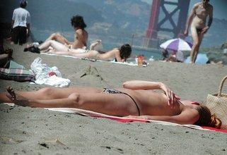 Hot girlfriend suntanns on a sandy beach