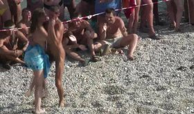 Completely naked guy and half naked babe are dancing on beach