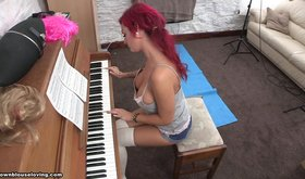 Redheaded seductress playing the piano with her tits out
