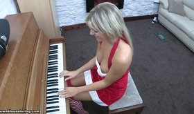 Tanned blonde playing the piano while looking sexy