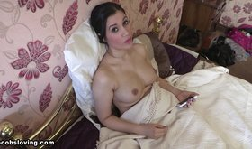 Busty brunette flips through her phone, acts naughty