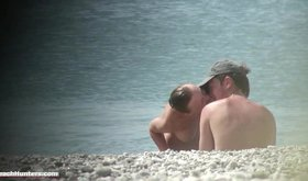 Young couple getting cozy on a nudist beach in front of everyone