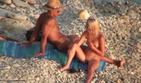 Nudist beach shenanigans featuring a really tanned blonde